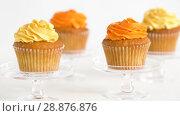 Купить «cupcakes with frosting on confectionery stands», видеоролик № 28876876, снято 13 июля 2018 г. (c) Syda Productions / Фотобанк Лори