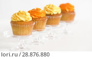 Купить «cupcakes with frosting on confectionery stands», видеоролик № 28876880, снято 13 июля 2018 г. (c) Syda Productions / Фотобанк Лори