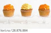 Купить «cupcakes with frosting on confectionery stands», видеоролик № 28876884, снято 13 июля 2018 г. (c) Syda Productions / Фотобанк Лори