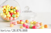 Купить «close up of scattered candy drops and jar on table», видеоролик № 28876888, снято 13 июля 2018 г. (c) Syda Productions / Фотобанк Лори