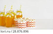 Купить «lemonade or juice in glass bottles and popcorn», видеоролик № 28876896, снято 13 июля 2018 г. (c) Syda Productions / Фотобанк Лори