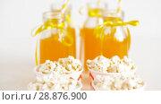 Купить «lemonade or juice in glass bottles and popcorn», видеоролик № 28876900, снято 13 июля 2018 г. (c) Syda Productions / Фотобанк Лори