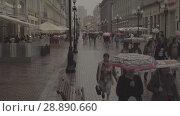 Купить «People walks on Old Arbat street during rainy summer day. Moscow downtown», видеоролик № 28890660, снято 24 июля 2018 г. (c) Ирина Мойсеева / Фотобанк Лори