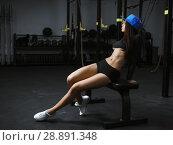 Купить «A beautiful sporty brunette is standing in the gym next to the barbells», фото № 28891348, снято 24 февраля 2018 г. (c) Restyler Viacheslav / Фотобанк Лори