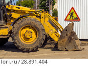 "Купить «Dirty quarry loader standing across the repaired street next to the sign ""road works"" hanging on the temporary fence», фото № 28891404, снято 4 августа 2018 г. (c) Евгений Харитонов / Фотобанк Лори"