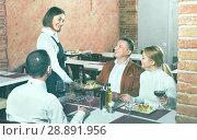 Купить «Female waiter bringing order to visitors», фото № 28891956, снято 20 сентября 2018 г. (c) Яков Филимонов / Фотобанк Лори