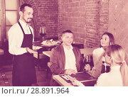 Купить «Male waiter bringing order to visitors», фото № 28891964, снято 16 января 2019 г. (c) Яков Филимонов / Фотобанк Лори