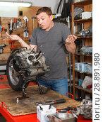 Купить «Male mechanic reconditioning modern moto», фото № 28891980, снято 8 мая 2018 г. (c) Яков Филимонов / Фотобанк Лори