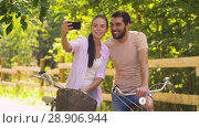 Купить «couple with bicycles taking selfie by smartphone», видеоролик № 28906944, снято 27 июля 2018 г. (c) Syda Productions / Фотобанк Лори
