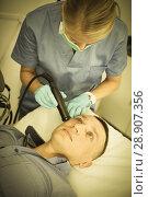 Купить «Woman doctor is doing vacuum massage procedure on face of adult client», фото № 28907356, снято 20 октября 2018 г. (c) Яков Филимонов / Фотобанк Лори