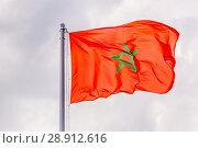Купить «The national flag of Morocco is fluttering in the wind against a blue cloudy sky.», фото № 28912616, снято 21 июня 2018 г. (c) Акиньшин Владимир / Фотобанк Лори