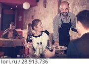 Купить «waiter bringing ordered dishes to smiling couple», фото № 28913736, снято 18 декабря 2017 г. (c) Яков Филимонов / Фотобанк Лори