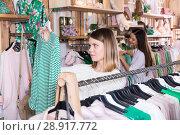 Купить «Woman customer looking green striped long sleeve shirt in store», фото № 28917772, снято 15 марта 2018 г. (c) Яков Филимонов / Фотобанк Лори