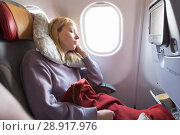 Купить «Tired blonde casual caucasian lady sleepin on seat while traveling by airplane. Commercial transportation by planes.», фото № 28917976, снято 21 ноября 2019 г. (c) Matej Kastelic / Фотобанк Лори