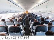 Купить «Interior of commercial airplane with passengers on their seats during flight.», фото № 28917984, снято 24 июня 2019 г. (c) Matej Kastelic / Фотобанк Лори
