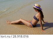 Купить «Outdoor summer lifestyle portrait of pretty young suntanned woman in a hat sitting at sea sunbathe. Beach travel. Summer vibes», фото № 28918016, снято 4 августа 2018 г. (c) Happy Letters / Фотобанк Лори