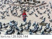 Купить «The boy stands in the square among a large flock of pigeons on 13 April 2018 in Kathmandu, Nepal», фото № 28926144, снято 13 апреля 2018 г. (c) Валерий Смирнов / Фотобанк Лори