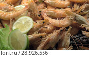Купить «A closeup of cooked shrimpes decorated with lemon and lettuce», видеоролик № 28926556, снято 1 марта 2018 г. (c) Данил Руденко / Фотобанк Лори