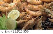 Купить «A closeup of cooked shrimpes decorated with lemon and lettuce», видеоролик № 28926556, снято 1 марта 2018 г. (c) Данил Руденко / Фотобанк Лори