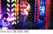 Купить «Modern young people playing laser tag on dark labyrinth in bright beams of laser pistols», видеоролик № 28936180, снято 21 мая 2018 г. (c) Яков Филимонов / Фотобанк Лори