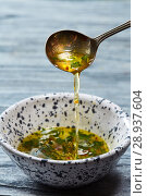 Homemade salad dressing with olive oil, vinegar, greens and spices pour from a spoon into a bowl on a gray wooden table. Стоковое фото, фотограф Ярослав Данильченко / Фотобанк Лори