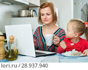 Купить «Smiling woman sitting in the kitchen with daughter», фото № 28937940, снято 14 августа 2018 г. (c) Яков Филимонов / Фотобанк Лори
