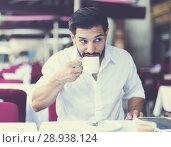 Купить «Man drinking coffee in summer cafeteria», фото № 28938124, снято 5 августа 2017 г. (c) Яков Филимонов / Фотобанк Лори