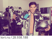 Купить «Nice man in moto jacket is choosing new gloves», фото № 28938188, снято 1 сентября 2017 г. (c) Яков Филимонов / Фотобанк Лори
