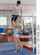 Купить «Man and woman doing acrobatic exercises in gym», фото № 28938264, снято 18 июля 2018 г. (c) Яков Филимонов / Фотобанк Лори