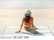 Купить «Summer lifestyle portrait of pretty young suntanned woman in a hat. Enjoying life and sitting on the beach, time to travel. Looking at the sea», фото № 28947940, снято 4 августа 2018 г. (c) Happy Letters / Фотобанк Лори