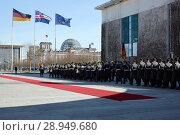 Berlin, Germany - View of the Ehrenhof of the Federal Chancellery with the red carpet for state visit from Iceland. The staff band and the guard battalion march in. (2018 год). Редакционное фото, агентство Caro Photoagency / Фотобанк Лори