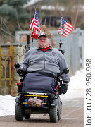 Neuenhagen, man drives his US-flagged electric wheelchair on the day of the swearing-in of US President Donald Trump (2017 год). Редакционное фото, агентство Caro Photoagency / Фотобанк Лори