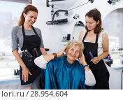 Купить «Hairstylists presenting result of styling to female client», фото № 28954604, снято 26 июня 2018 г. (c) Яков Филимонов / Фотобанк Лори