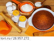 Купить «Freshly baked homemade cake in ceramic form and ingredients for dough preparation: chicken eggs, sugar, flour and spices on a wooden background. Culinary Still Life. Top view», фото № 28957272, снято 16 июля 2018 г. (c) Виктория Катьянова / Фотобанк Лори