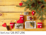 Купить «Christmas handmade gifts - a congratulatory letter, red soft X-mas toys and branches of a Christmas tree with cones on a wooden background. Top view. Space for text. New Year still life», фото № 28957296, снято 25 июля 2018 г. (c) Виктория Катьянова / Фотобанк Лори