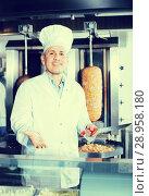Купить «Chef on cutting meat for kebab with steel knife», фото № 28958180, снято 15 октября 2018 г. (c) Яков Филимонов / Фотобанк Лори