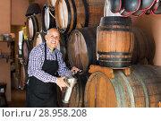 Купить «Positive mature man seller pouring wine from wood», фото № 28958208, снято 20 августа 2018 г. (c) Яков Филимонов / Фотобанк Лори