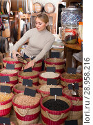 Купить «Adult cheerful woman buying dried beans», фото № 28958216, снято 18 августа 2018 г. (c) Яков Филимонов / Фотобанк Лори