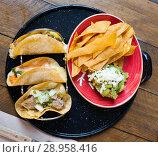 Купить «Top view of tacos with guacamole and nachos», фото № 28958416, снято 19 марта 2019 г. (c) Яков Филимонов / Фотобанк Лори