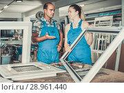 Купить «Worker helping female in work of assembling plastic windows», фото № 28961440, снято 19 июля 2017 г. (c) Яков Филимонов / Фотобанк Лори