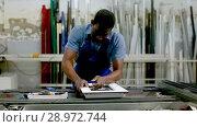 Купить «Male master is working with window frame in the window workshop.», видеоролик № 28972744, снято 23 мая 2018 г. (c) Яков Филимонов / Фотобанк Лори