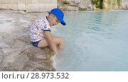 Купить «Child at travertine terrace in Pamukkale, Turkey», видеоролик № 28973532, снято 23 сентября 2018 г. (c) Данил Руденко / Фотобанк Лори