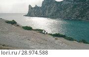 Купить «Aerial view woman walking against ocean and rocks», видеоролик № 28974588, снято 19 июля 2018 г. (c) Илья Шаматура / Фотобанк Лори