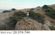Купить «Woman at the edge of the cliff», видеоролик № 28974744, снято 19 июля 2018 г. (c) Илья Шаматура / Фотобанк Лори