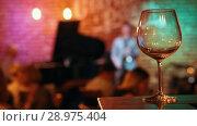 Купить «Empty wine glass on the bar, musicians in the background», видеоролик № 28975404, снято 4 апреля 2020 г. (c) Константин Шишкин / Фотобанк Лори