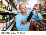 Купить «Portrait of joyful customer selecting wine», фото № 28976008, снято 4 июля 2018 г. (c) Яков Филимонов / Фотобанк Лори