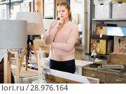 Купить «woman buyer standing in furniture shop choosing modern torchere indoors», фото № 28976164, снято 15 ноября 2017 г. (c) Яков Филимонов / Фотобанк Лори