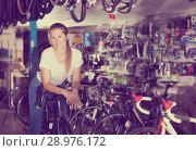 Купить «Young female is standing with bicycle in store», фото № 28976172, снято 13 сентября 2017 г. (c) Яков Филимонов / Фотобанк Лори