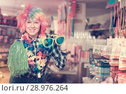 Купить «Girl in store of festival accessories», фото № 28976264, снято 15 марта 2018 г. (c) Яков Филимонов / Фотобанк Лори
