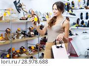 Купить «Woman looking after pair of shoes», фото № 28978688, снято 21 сентября 2018 г. (c) Яков Филимонов / Фотобанк Лори